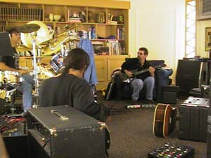 (copyright photo : David Koblentz) John Myung (de dos), Rod Morgenstein et Ty Tabor dans le salon de ce dernier (écriture de The Jelly Jam 2)
